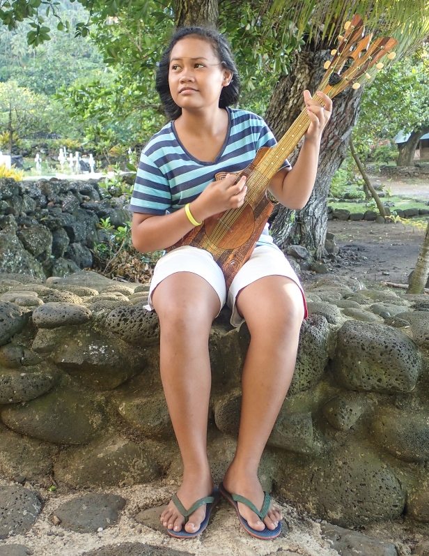 A vision from a painting by Paul Gauguin, this young girl plays her hand-carved guitar in front of a cemetery on the island Tahuata