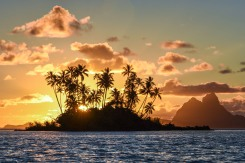 The tropical Polynesian island of Tahaa in the foreground with the majestic peaks of Bora Bora as a backdrop