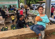 Young Alesha Muhuinga sips the juice of a fresh green coconut at the Saturday Market in the Port of Refuge, Tonga